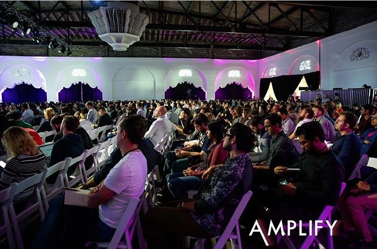 A large group of attendee's at Amplify Conference attendee's sat intently listening and watching a presentation