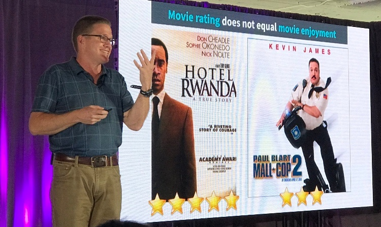 A smiling man wearing glasses and a polo shirt stood beside a screen presenting a comparison between two different film posters
