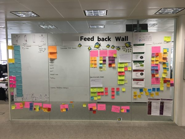 A photo of the feedback wall covered in post it notes