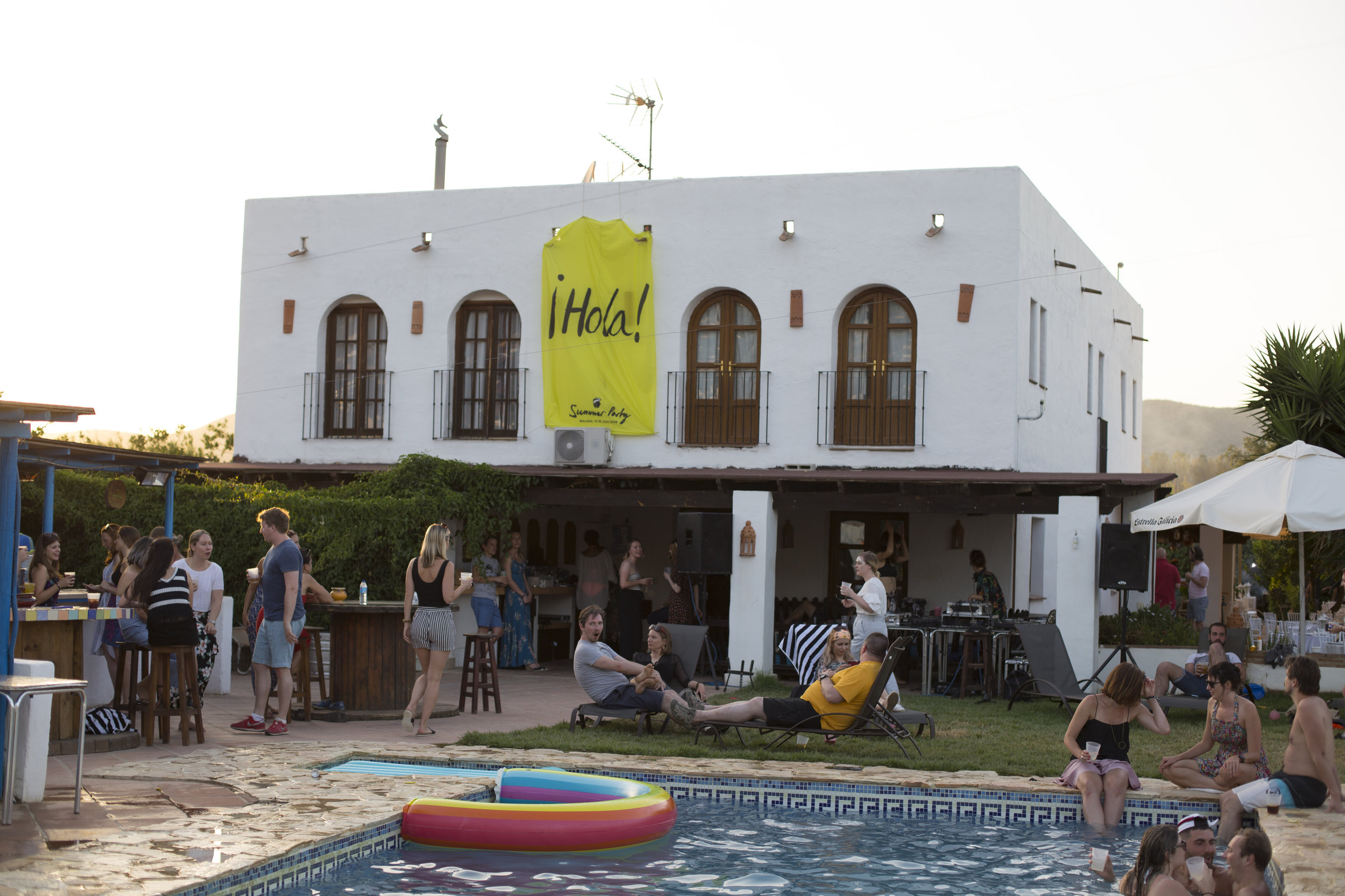 A photo outside of the hotel/villa with some people in the pool and others stood having a chat by the bar.