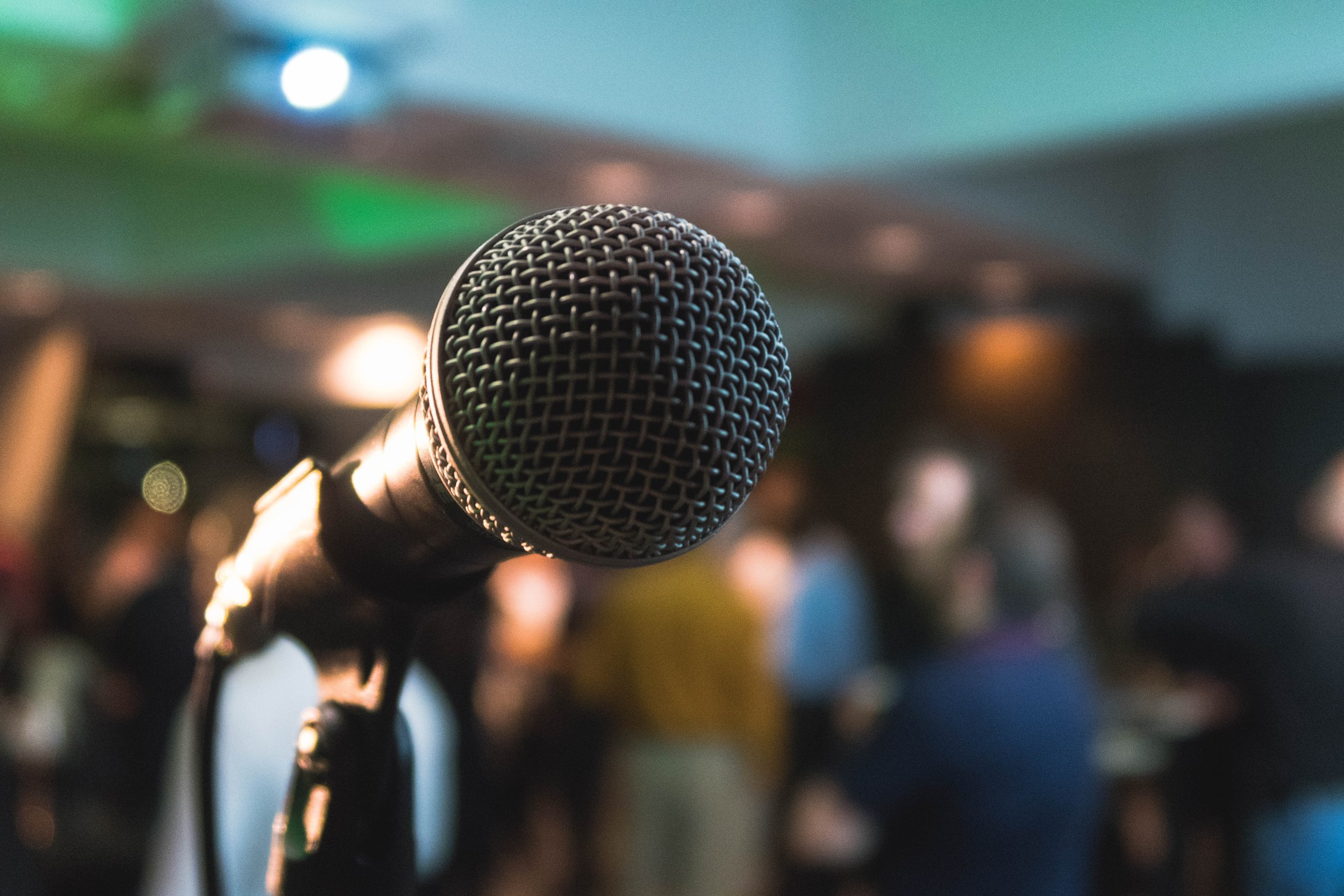 A black microphone on a stand with the background blurred out though it looks like some sort of event.