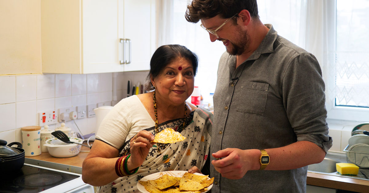A young man and an older woman stand smiling in a kitchen sharing a plate of flat breads.
