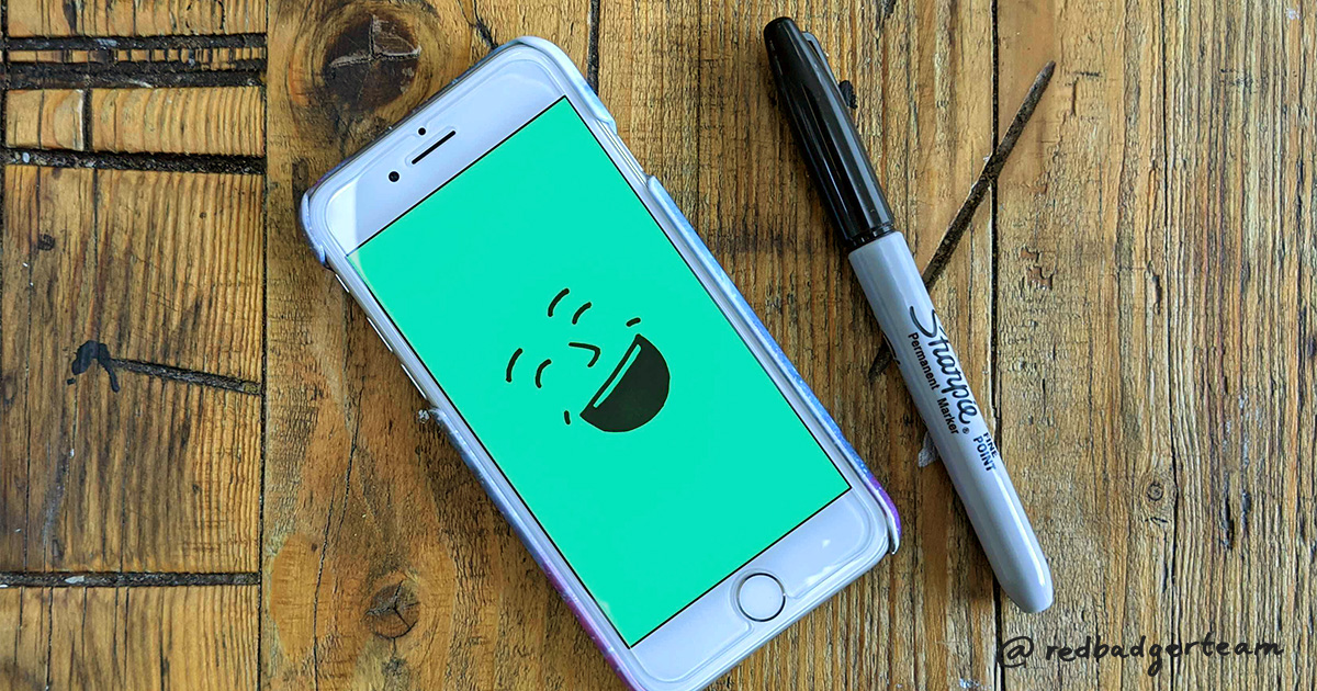 Illustration of laughing face on green background on a phone which is sat on a wooden table with a sharpie pen next to it