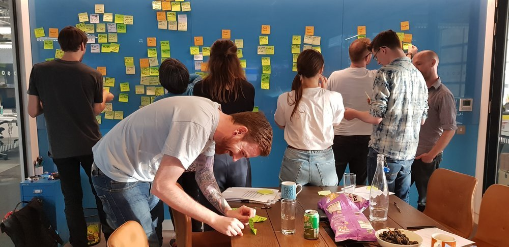 A photo of a meeting as everyone looks at the post it notes stuck up while one person rushes to finish his note.