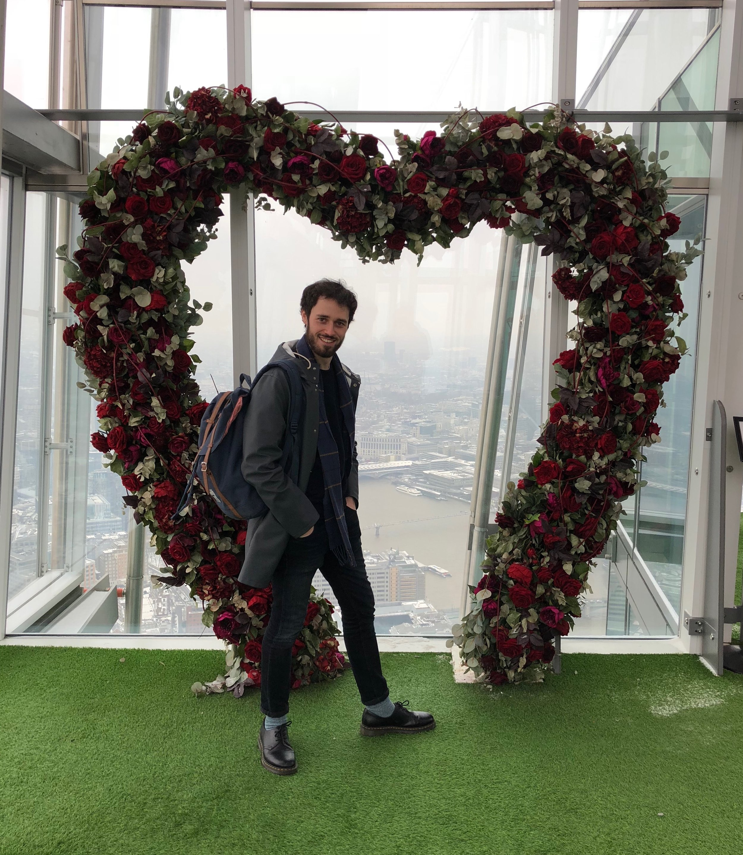 A smiling Tim stood inside a heart shaped rose arch
