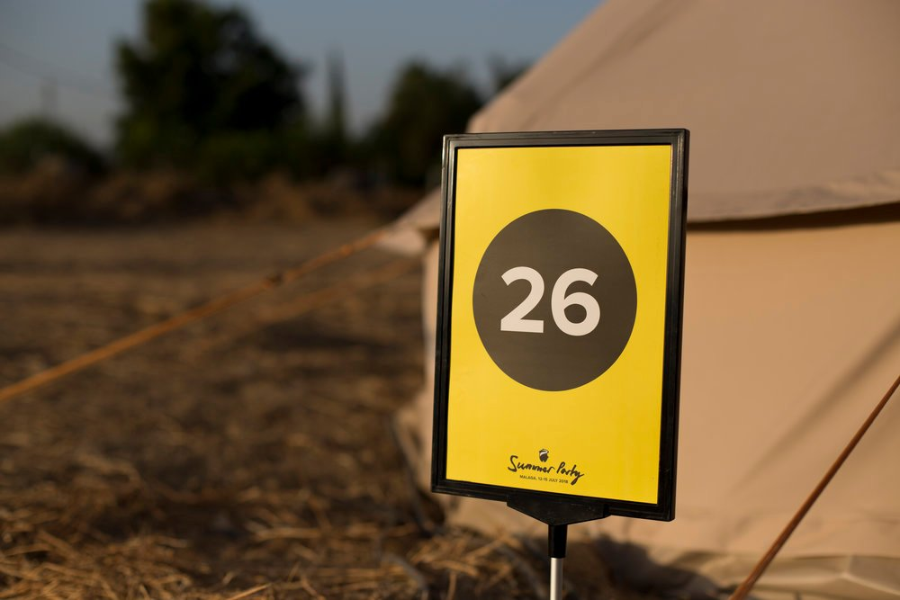 A yellow numbered post outside of a tent