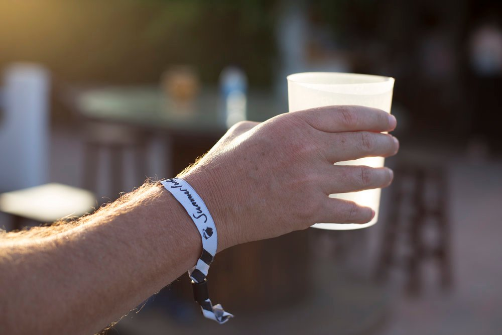 A closeup shot of a hand holding a drink with the 'Summer Party' wristband