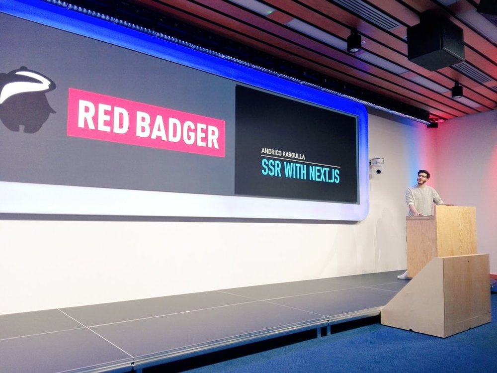 Andrico Karoulla stood at a podium beside a large screen with the Red Badger logo. (credit: Sonya Moisset @sonyamoisset)