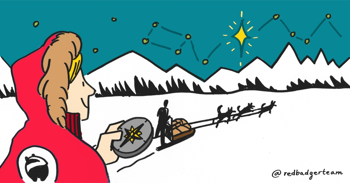 Woman in a Red Badger branded coat holding a compass and looking on to a sleigh surrounded by stars and mountains