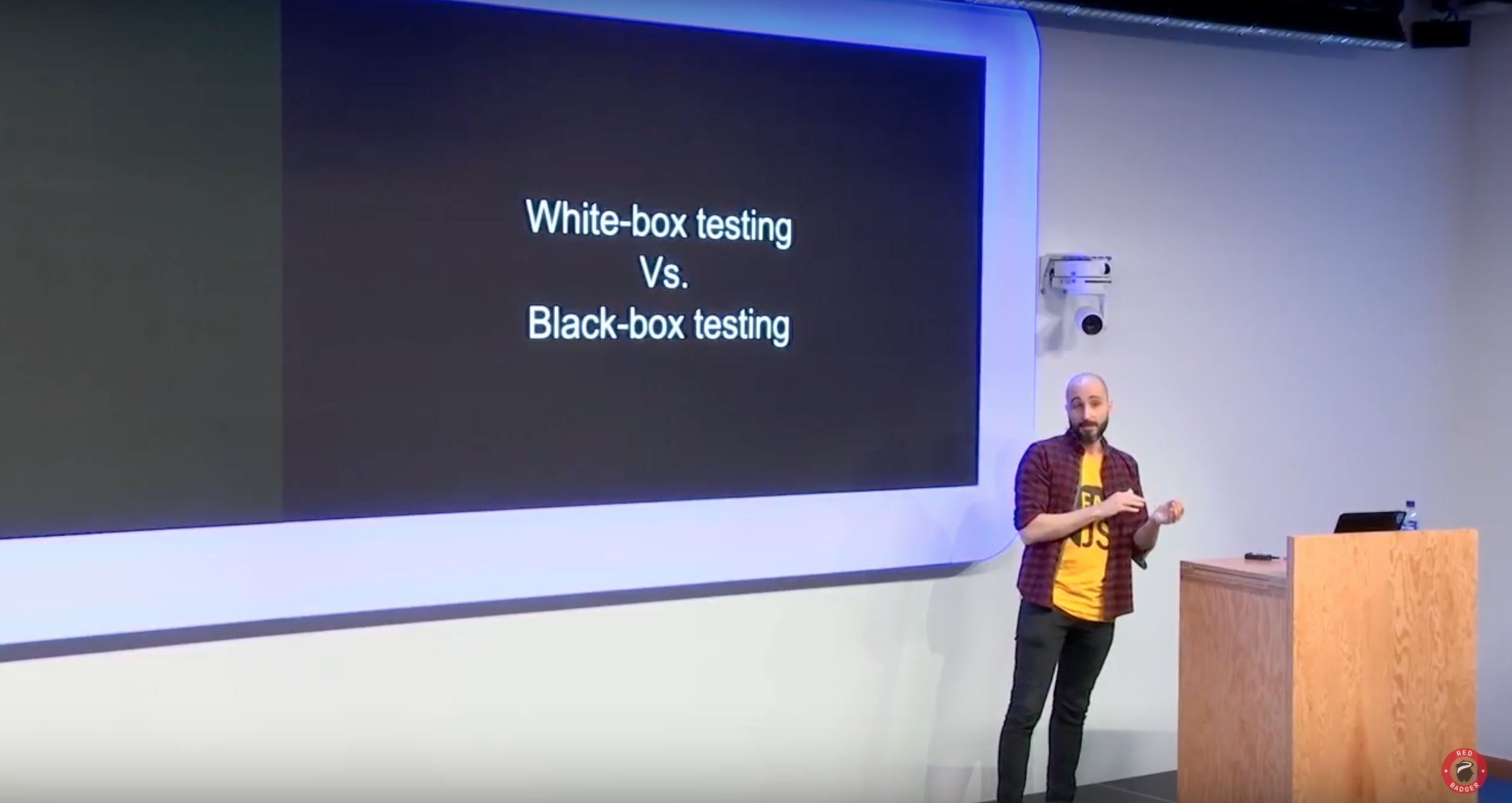 "A photo from the presentation where the speaker is stood beside the slide which says ""White-box testing vs Black-box testing"""
